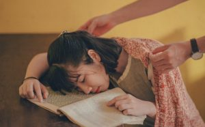 Girl asleep with head in her book